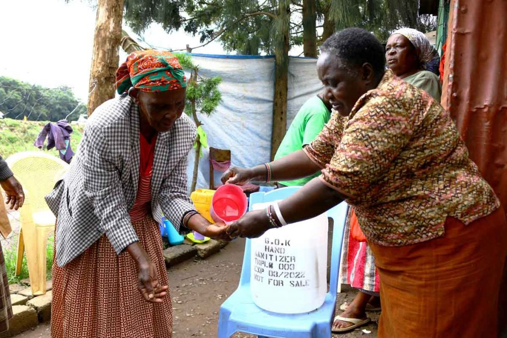 Agnes-Kariuki-L-demonstrates-how-a-government-of-Kenya-donated-hand-sanitizer-is-to-be-used.-1